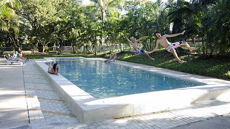 backpacker jumping in pool