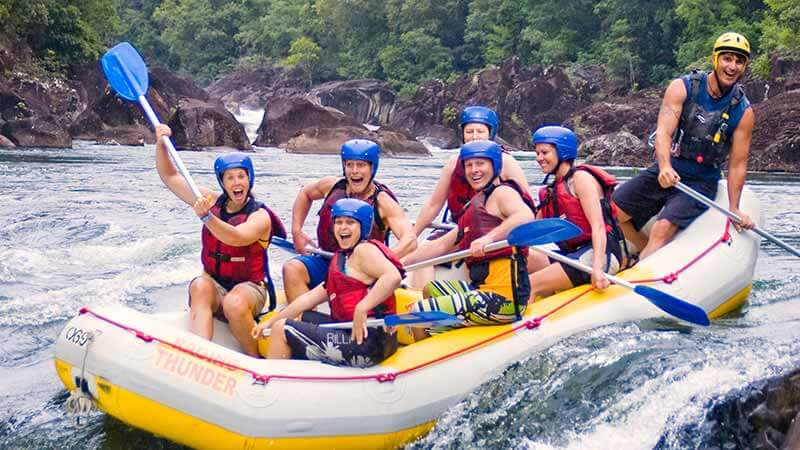 Group in the raft, paddles in the air