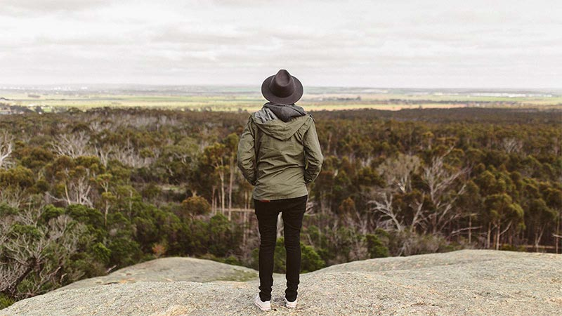 Girl on top of a mountain looking out over the Aussie bush landscape