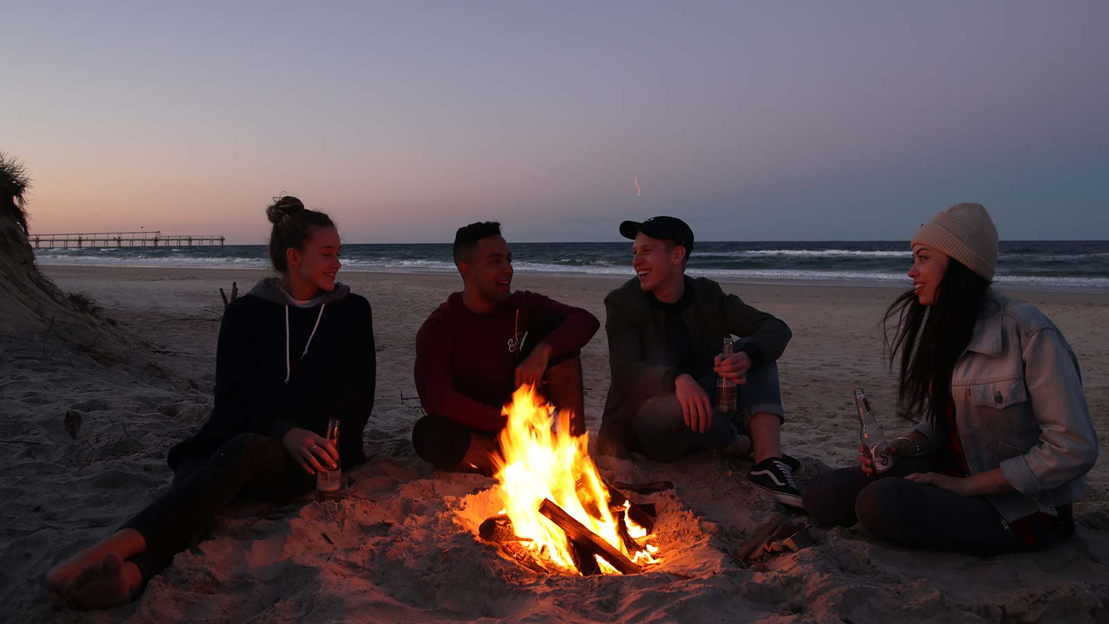 people around a campfire on the beach